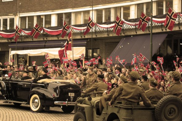 From the making of the Norwegian movie Max Manus  in 2008. The movie tells the story of Max Manus from the Norwegian resistant movement during the German occupation of Norway in World War II. The scene shown recapture the event when king Haakon returns home to Oslo and Norway after the war, riding in his car (A-1) together with his son, crown prince Olav. The newly freed people of Oslo celebrates the victory and the royal family with flags and cheering. (Photo: Kjetil Bjørnsrud)