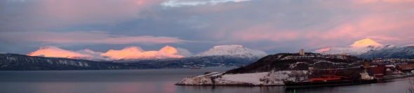 Low sun shines on the mountain peaks by the Ofoten Fjord