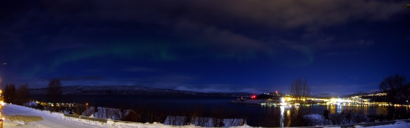 Northern light (aurora borrealis) with moon shining on the mountains in the background