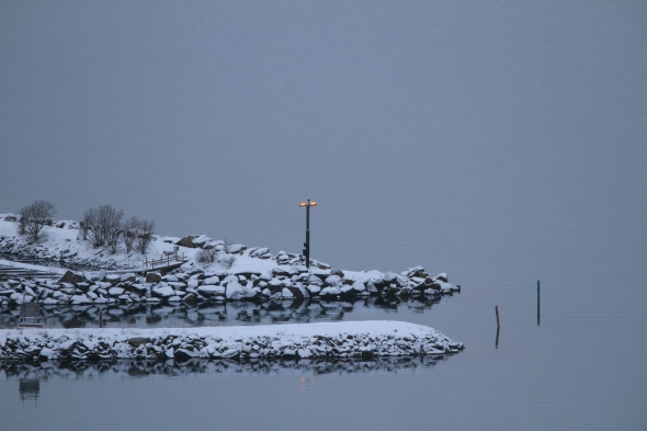 Breakwater at the Ankenes Marina with the runway light beacon for the minicipal airport