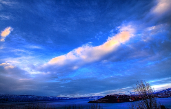HDR of the Narvik peninsula, the surrounding fjords and mountains underneath a sky with intermittent clouds