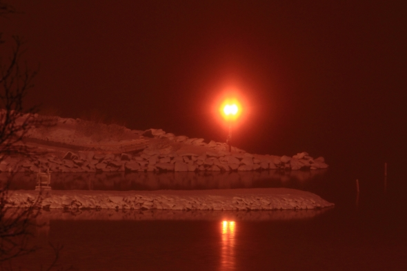 The airport beacon on the breakwater silently shines it's light on the water of The Ofoten Fjord