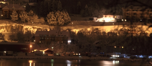 A long exposure from the waterfront in the city. The yellow blobs that stretches out horizontally, is just the snowplow's yellow, blinking warning light as it thunders into the Fagernes Tunnel