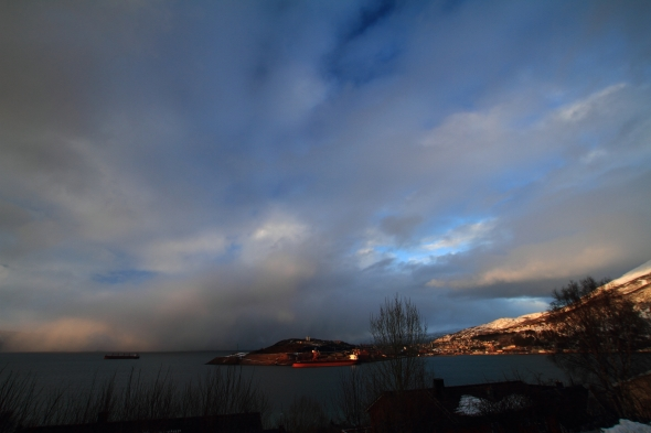 Evening sun shines on the city Narvik - in between the snow showers
