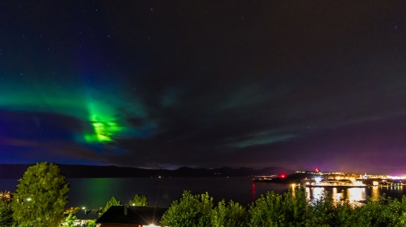 Northern Lights behind clouds reflecting into the Ofoten Fjord. Narvik peninsula to the right.