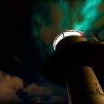 """The Light Machine"" - Lighthouse on Ankenes and Northern Lights behind fast moving clouds up above."